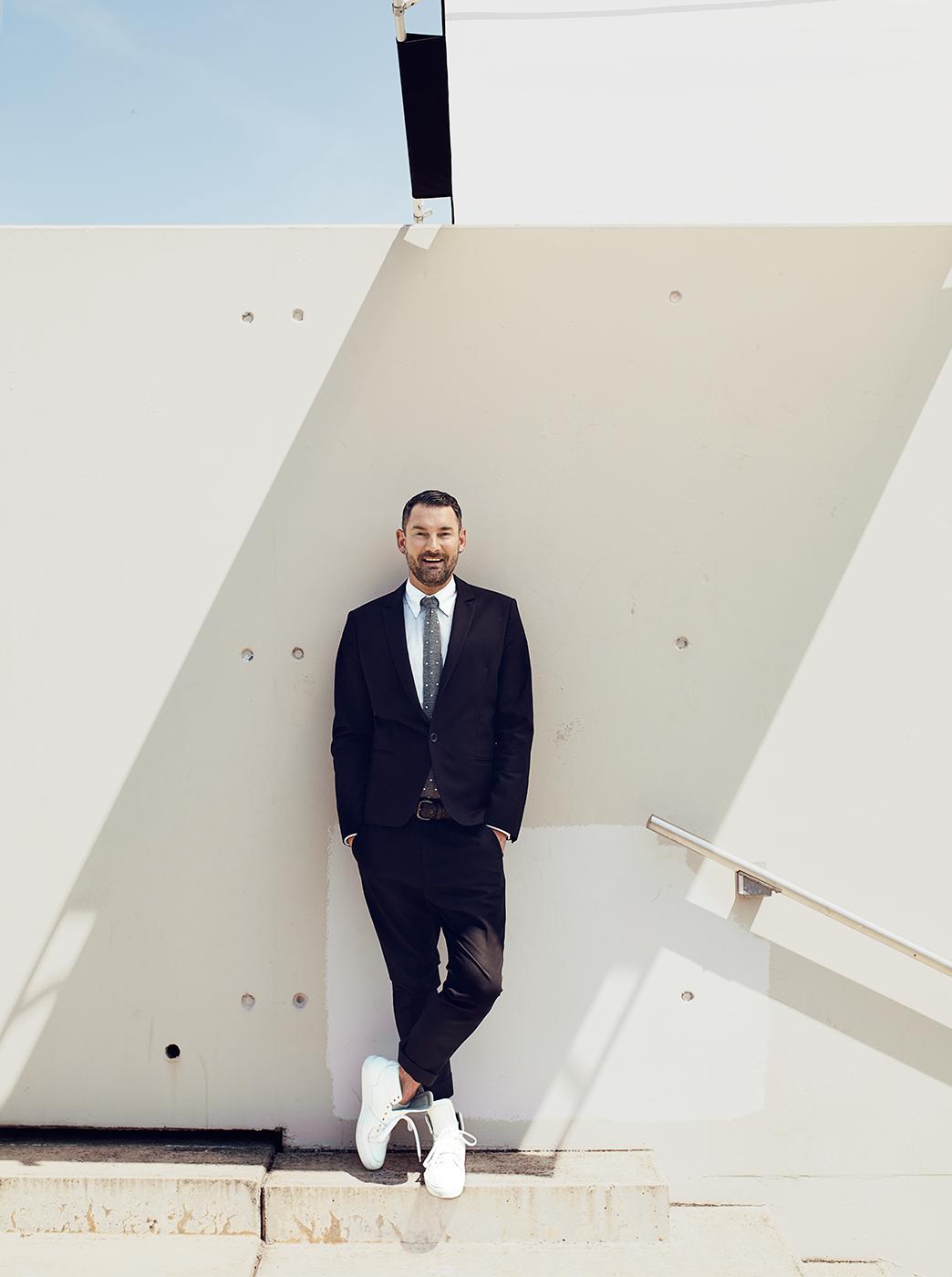 Foto Michael Michalsky im Anzug, Ganzkörperaufnahme vor heller Betonwand